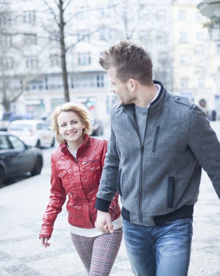 Glückliches junges Paarhändchenhalten beim Gehen auf Stadtstraße lizenzfreies stockbild
