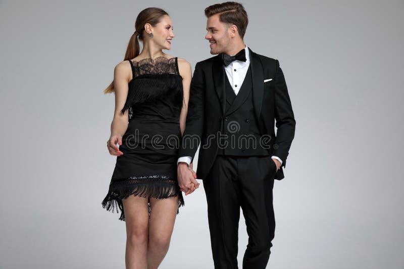 Glückliches junges Paarhändchenhalten und -c$lachen lizenzfreie stockbilder