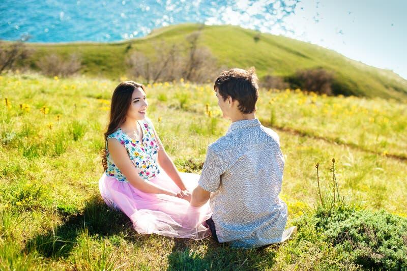 Glückliches junges Paarhändchenhalten und Lachen auf dem Strand lizenzfreie stockfotos