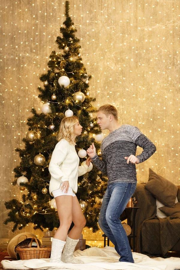 Glückliches junges Paartanzen durch den Weihnachtsbaum lizenzfreie stockfotografie