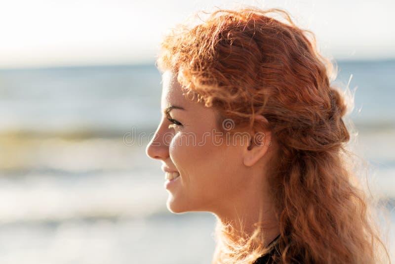 Glückliches junges Rothaarigefrauengesicht auf Strand lizenzfreies stockbild