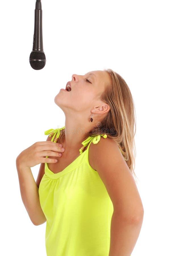 Glückliches junges schönes Mädchen, das mit Mikrofon singt stockfotografie