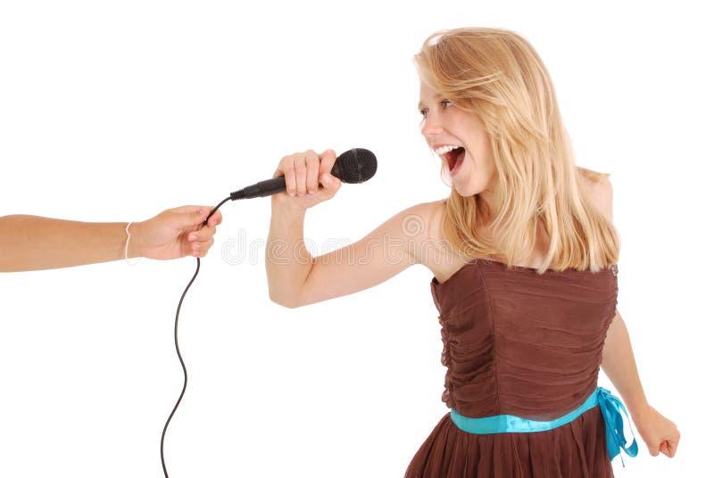 Glückliches junges schönes Mädchen, das mit Mikrofon singt lizenzfreies stockfoto