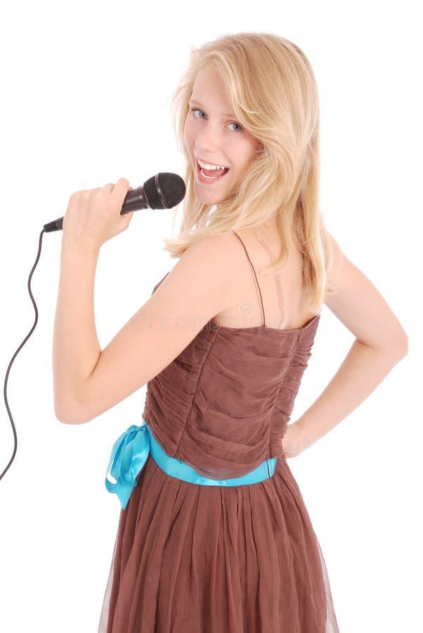 Glückliches junges schönes Mädchen, das mit Mikrofon singt stockbild