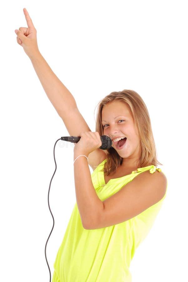 Glückliches junges schönes Mädchen, das mit Mikrofon singt stockfoto