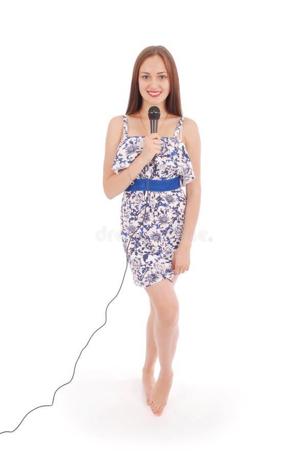 Glückliches junges schönes Mädchen, das mit Mikrofon singt lizenzfreie stockfotos