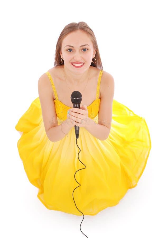 Glückliches junges schönes Mädchen, das mit Mikrofon singt lizenzfreie stockfotografie