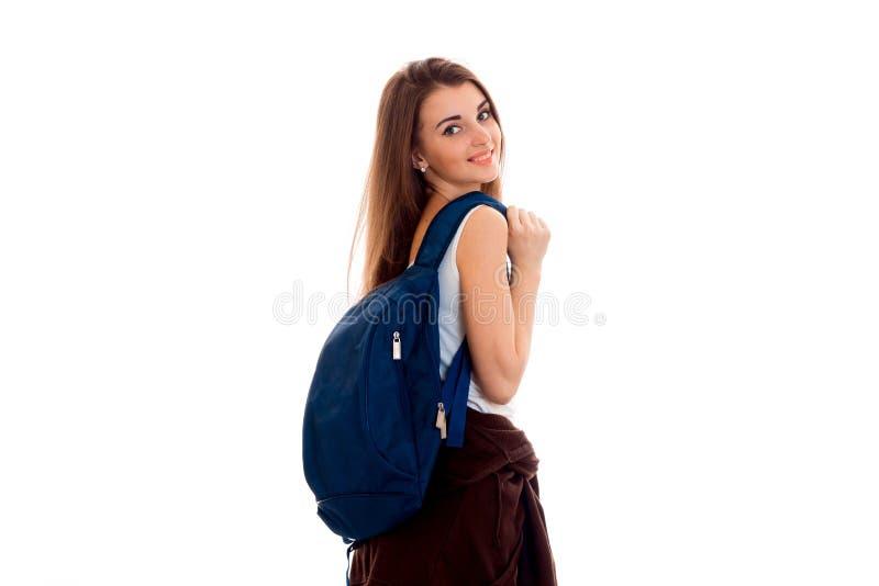 Glückliches junges Studentenmädchen mit blauem Rucksack auf Schulter lächelnd auf der Kamera lokalisiert auf weißem Hintergrund stockbild
