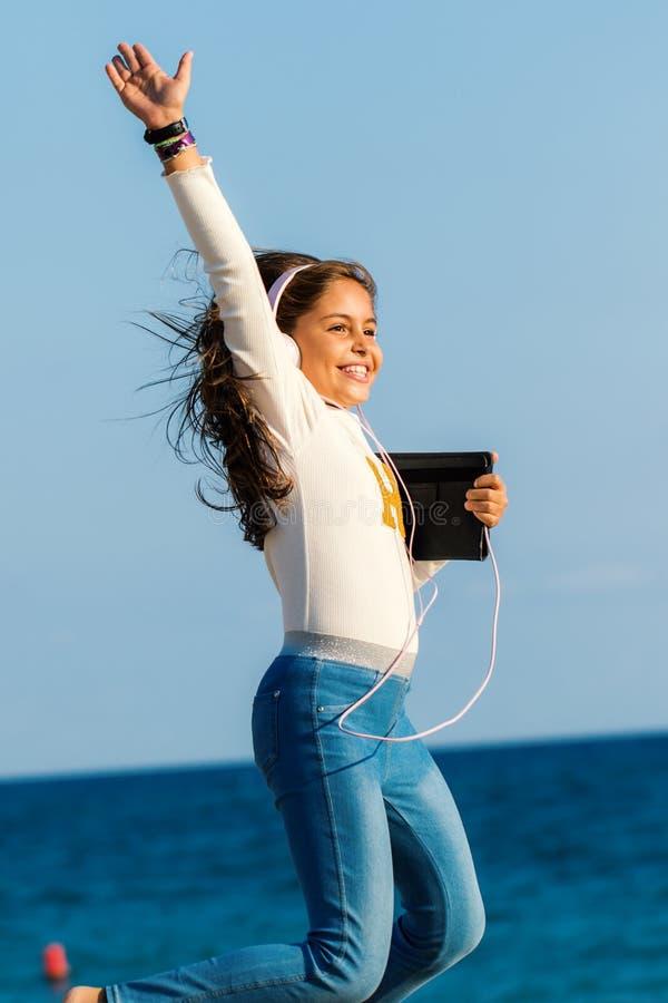 Glückliches junges Tweenmädchen, das mit Kopfhörern und Tablette auf Strand springt lizenzfreie stockfotografie