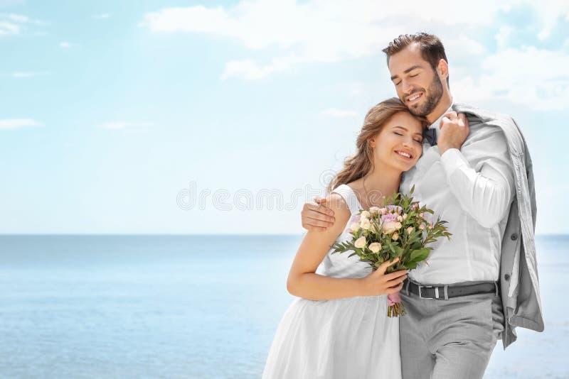 Glückliches Jungvermähltenpaarumarmen lizenzfreies stockbild