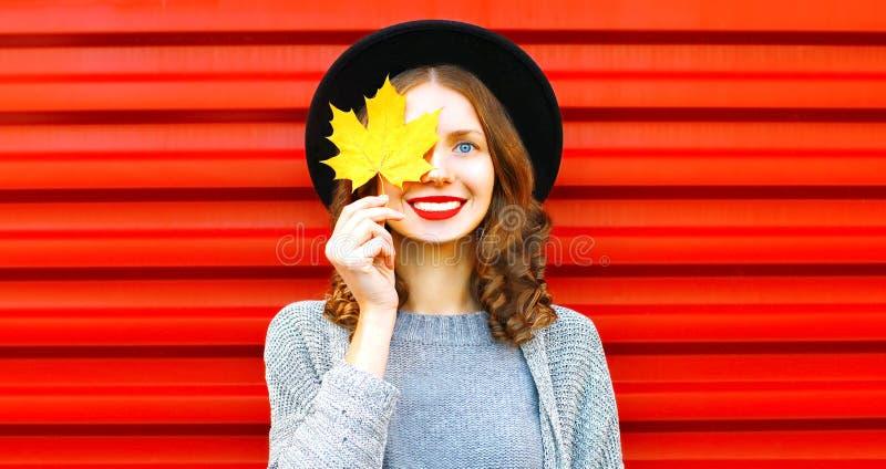 Glückliches kühles Mädchen versteckt ein gelbes Ahornblatt des Auges auf einem Rot stockfotos