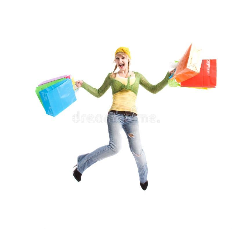 Glückliches kaukasisches Mädchen, das mit Einkaufenbeuteln springt lizenzfreie stockfotos