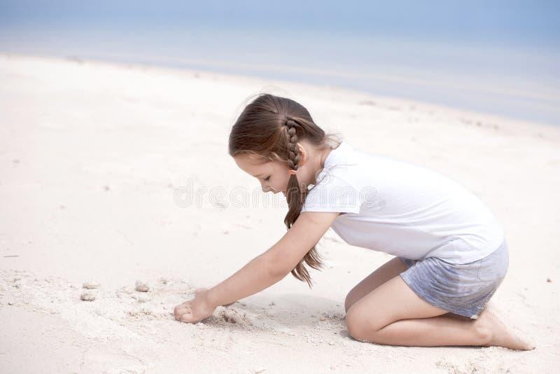 Glückliches Kind auf dem Strand Paradiesfeiertagskonzept, Mädchensitzplätze auf sandigem Strand mit blauem seichtem Wasser und sa lizenzfreie stockbilder