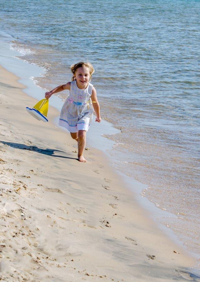 Glückliches Kind, das auf Strand mit Spielzeugboot läuft stockfotografie