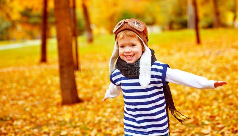 Glückliches Kind, das draußen Versuchsflieger im Herbst spielt lizenzfreies stockfoto