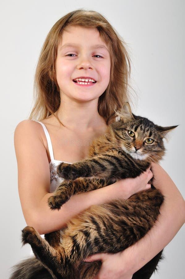 Glückliches Kind, das eine Katze in den Händen anhält lizenzfreies stockfoto