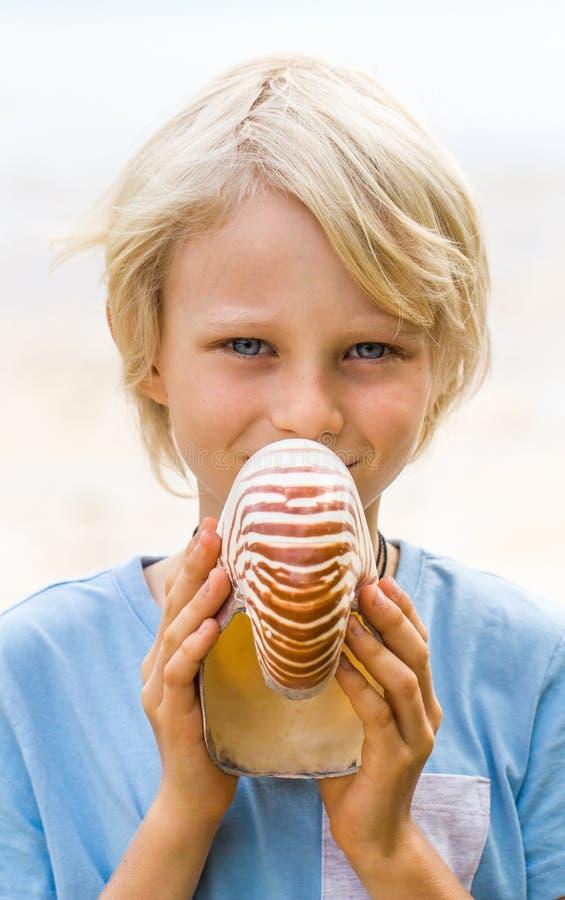 Glückliches Kind, das eine Nautilusmuschel hält stockfotos