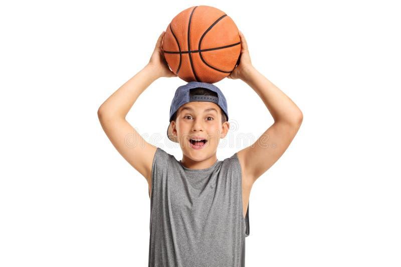 Glückliches Kind, das einen Basketball hält und die Kamera betrachtet lizenzfreie stockbilder