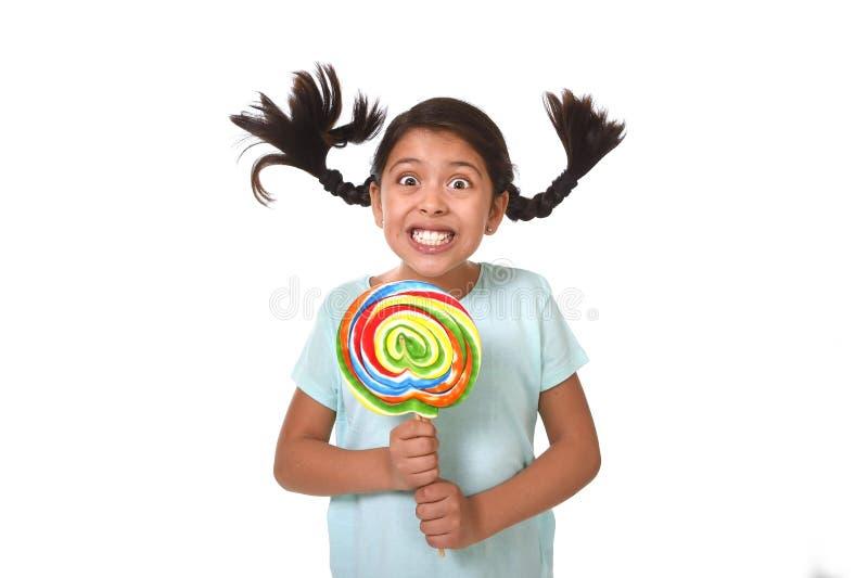 Glückliches Kind, das große Lutschersüßigkeit mit den Pferdeschwänzen fliegen in ungewöhnliches verrücktes lustiges Gesicht hält lizenzfreie stockfotos