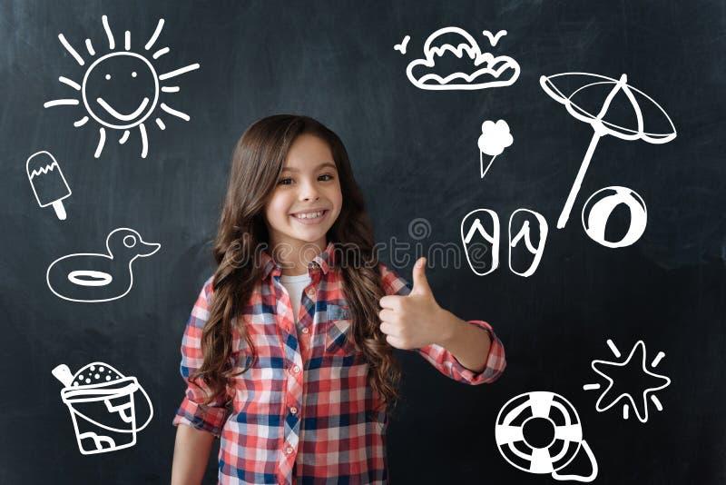 Glückliches Kind, das ihren Daumen aufstellt und auf Sommerferien wartet stockfotografie