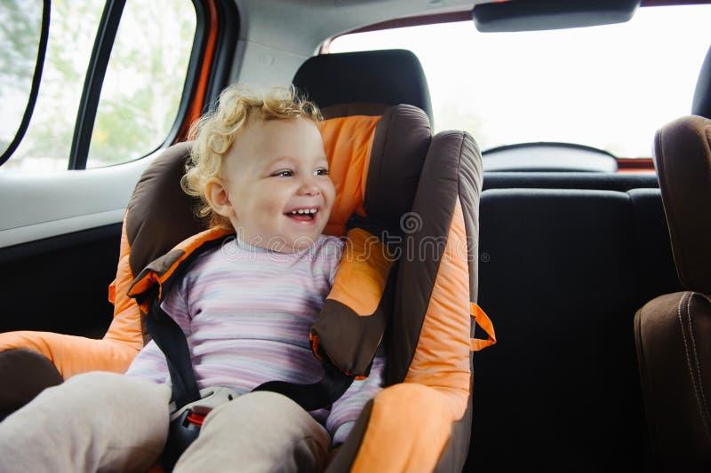 Glückliches Kind, das im Autositz lächelt stockbilder