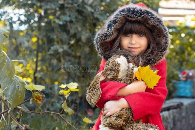 Glückliches Kind, das im Herbstpark spielt Kind, das gelben Herbstlaub erfasst lizenzfreies stockbild