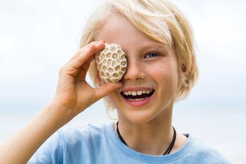 Glückliches Kind, das korallenrotes Über sein Auge hält stockbild