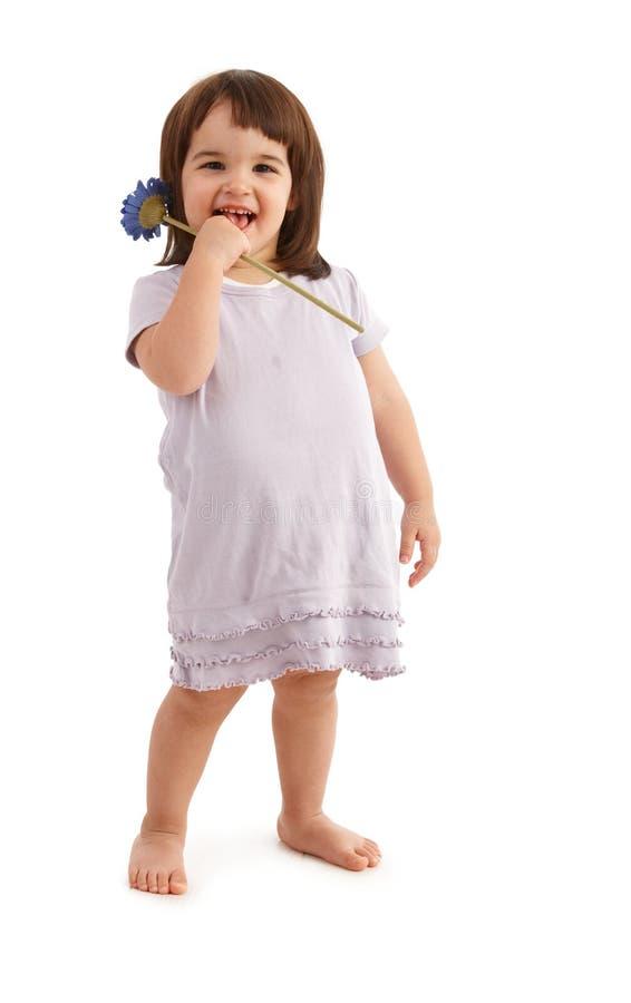 Glückliches Kind, das mit Blume aufwirft stockbild