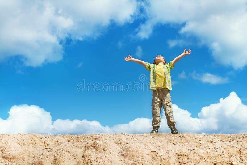 Glückliches Kind, das mit den Händen angehoben oben über Himmel steht stockfoto