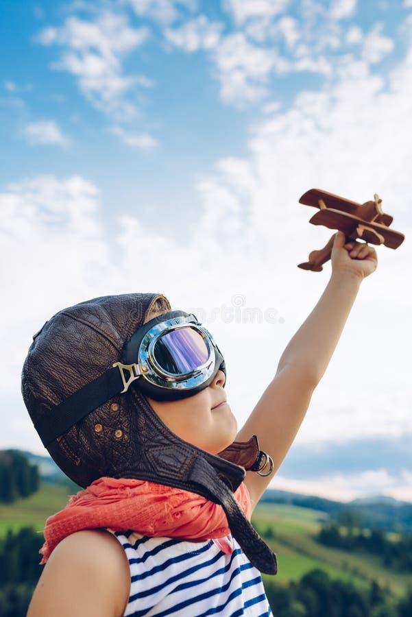 Glückliches Kind, das mit hölzernem Spielzeugflugzeug gegen blauen Sommer s spielt stockfotos