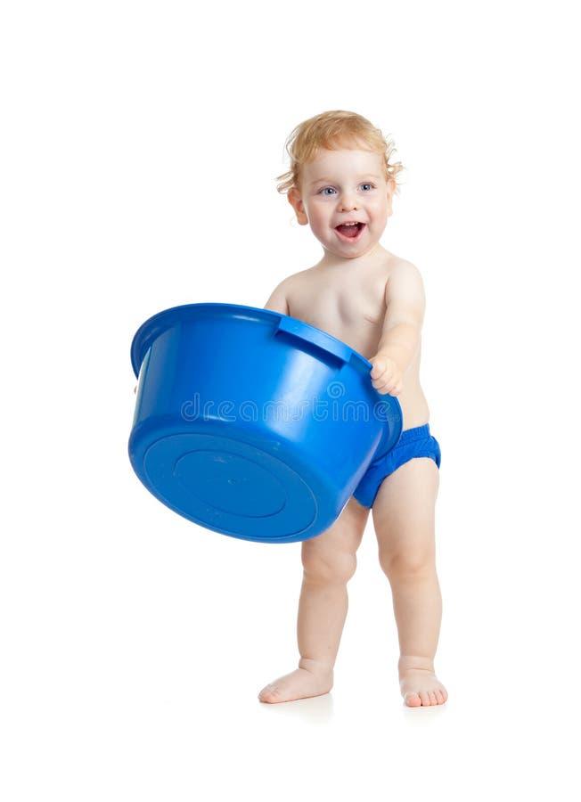 Glückliches Kind, das mit Plastikwäscheschüssel steht stockfotografie