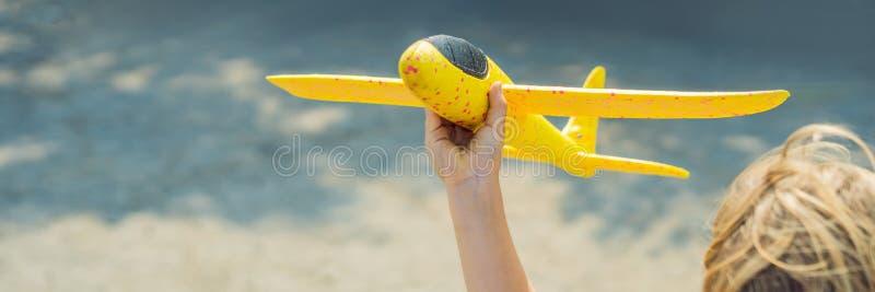 Glückliches Kind, das mit Spielzeugflugzeug gegen alten Rollbahnhintergrund spielt Mit Kinderkonzept FAHNE reisen, LANGES FORMAT lizenzfreie stockfotografie