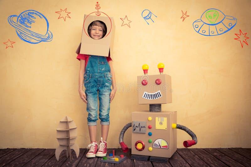 Glückliches Kind, das mit Spielzeugroboter spielt lizenzfreies stockfoto