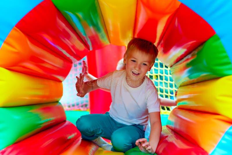 Glückliches Kind, das Spaß auf Spielplatz im Kindergarten hat stockbilder