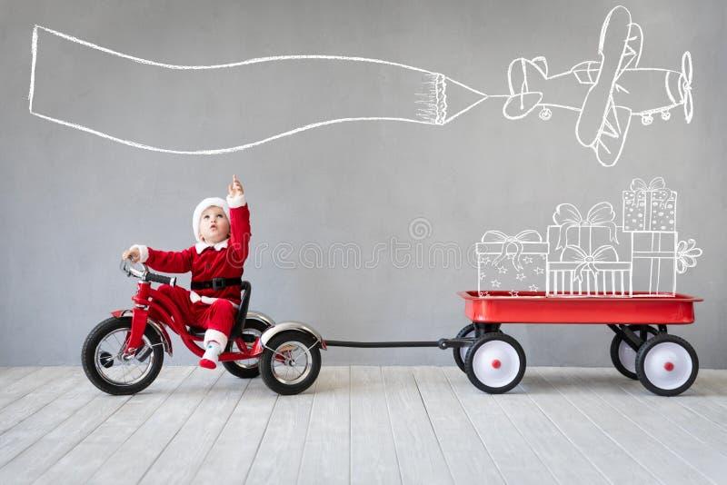 Glückliches Kind, das Spaß auf Weihnachtszeit hat stockfoto