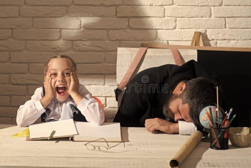 Glückliches Kind, das Spaß hat Schulmädchen mit entsetztem Gesicht und ihr schlafender Tutor stockfotografie