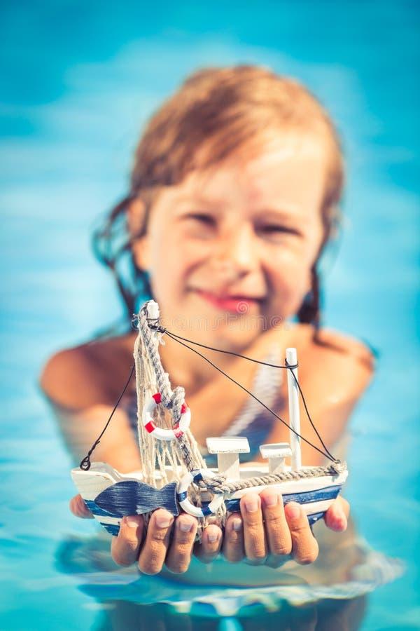 Glückliches Kind, das Spielzeugsegelboot in den Händen hält lizenzfreies stockfoto