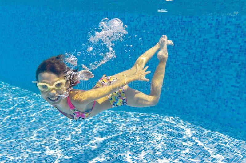 Glückliches Kind, das underwater im Pool schwimmt lizenzfreies stockfoto
