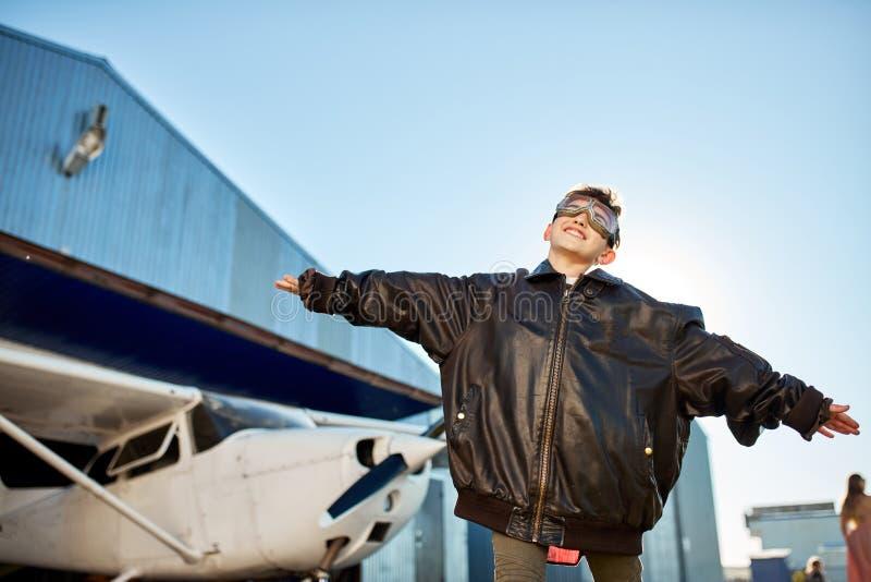 Glückliches Kind in den Fliegergläsern, die vor weißem hellem Privatflugzeug spielen stockfotografie