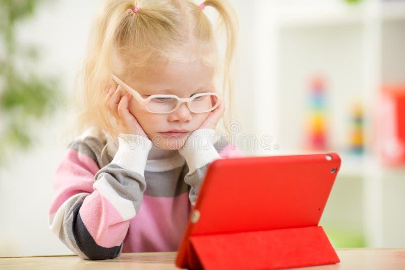 Glückliches Kind in den Gläsern, die Minitabletten-PC betrachten stockfotografie