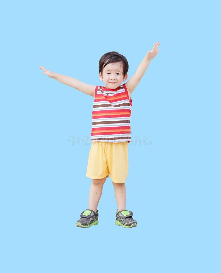 Glückliches Kind der Nahaufnahme seine Hand anheben und Arme wie Fliegen mit dem Lächelngesicht verbreiten lokalisiert auf blau stockfotografie