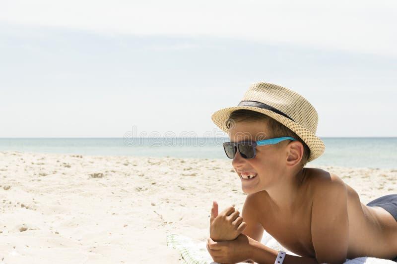 Glückliches Kind in der Sonnenbrille und im Hut auf Strand Reisenkoffer mit Meerblick nach innen lizenzfreies stockbild