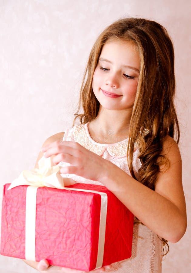 Glückliches Kind des kleinen Mädchens, das rote Geschenkbox in der Weihnachtszeit öffnet lizenzfreies stockbild