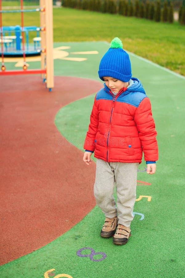 Glückliches Kind draußen Netter kleiner Junge, der auf buntem modernem Spielplatz spielt Kind haben Spaß in der kalten Zeit Glück lizenzfreie stockfotografie