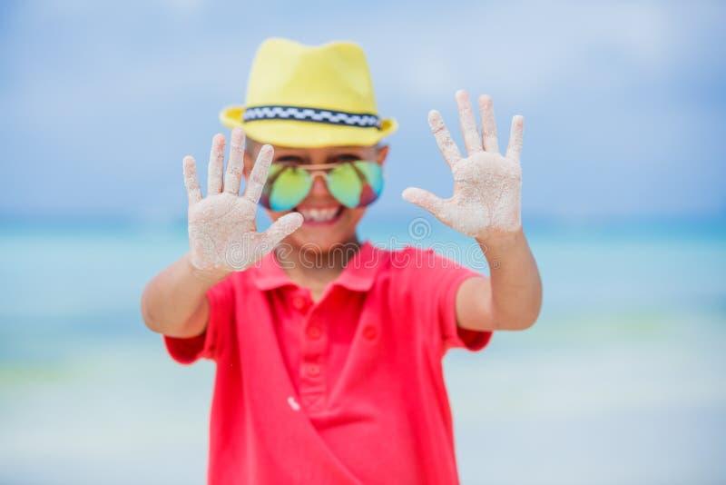 Glückliches Kind im gelben Hut und in der Sonnenbrille auf Strand Reisenkoffer mit Meerblick nach innen lizenzfreie stockbilder