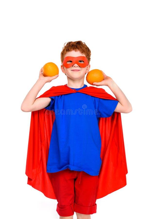 glückliches Kind im Superheldkostüm, das Orangen hält und an der Kamera lächelt stockfotografie