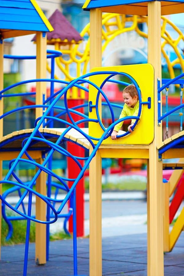 Glückliches Kind, Junge, der Spaß auf Spielplatz im Kindergarten hat stockfotografie