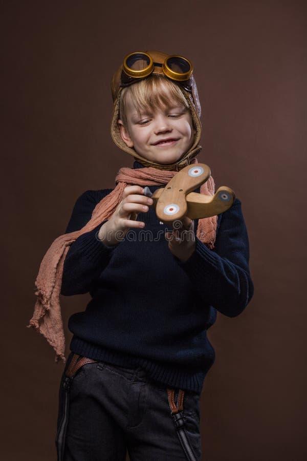 Glückliches Kind kleidete im Versuchshut und in den Gläsern an Kind, das mit hölzernem Spielzeugflugzeug spielt Traum und Freihei stockbild