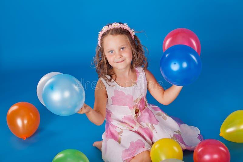 Glückliches Kind mit bunten Luft Ballons über Blau lizenzfreies stockfoto