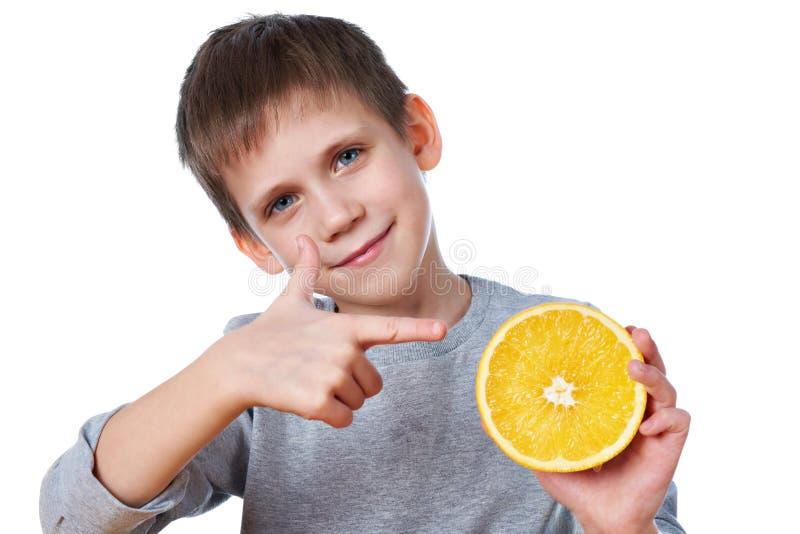 Glückliches Kind mit der Orange lokalisiert auf Weiß stockbild